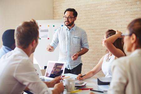 idée: Homme d'affaires moderne expliquer ses idées à ses collègues lors d'un séminaire
