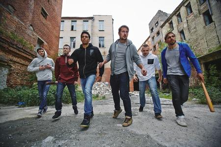 Group of spiteful hooligans walking along grunge brick houses Stock Photo