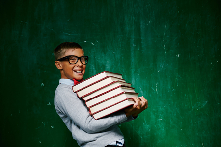 schoolkid: Cheerful schoolkid with stack of books looking at camera