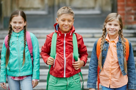 school boy: Group of cute schoolmates with backpacks looking at camera Stock Photo