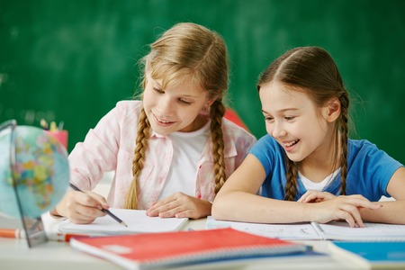 elementary schools: Two cute schoolgirls drawing together at lesson