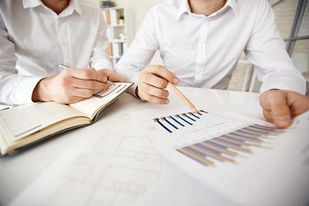 explaining: Group of businessmen explaining chart and making notes