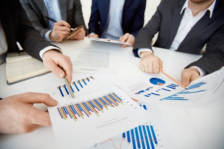 information point: Two co-workers pointing at charts while comparing them Stock Photo