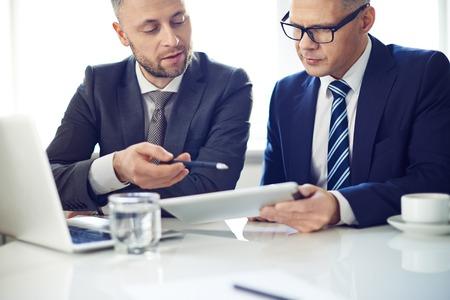 negocio: Dos hombres elegantes que usa la tableta digital de reunión