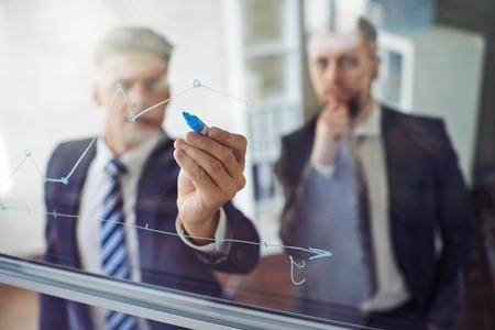 ejecutivos: De negocios que explica el gráfico a su colega