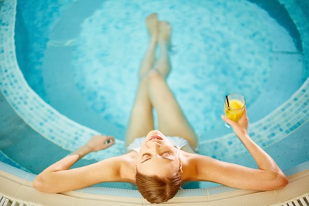 jacuzzi: Beautiful girl in bikini relaxing in swimming pool Stock Photo