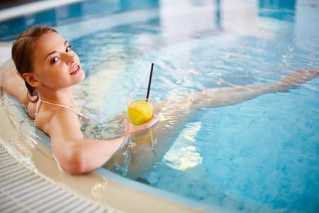 수영장에서 휴식하는 동안 주스의 유리를 들고 비키니 입은 젊은 여성