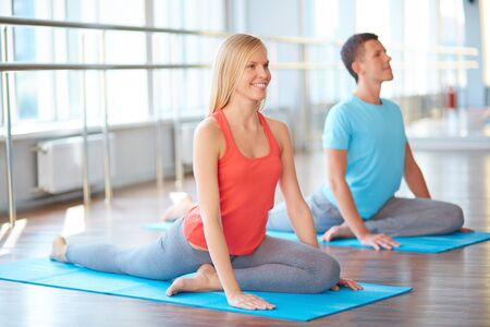 woman stretching: Pretty girl doing yoga exercise in gym with guy on background