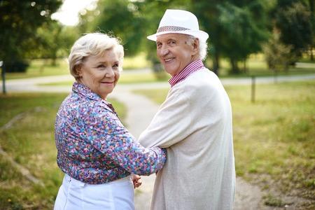 ancianos caminando: Feliz pareja senior mirando a la cámara durante la caminata