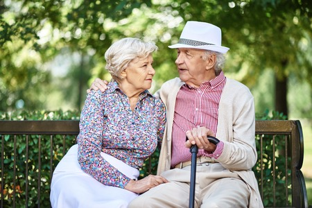 restful: Restful seniors in smart casual sitting on bench in park and talking
