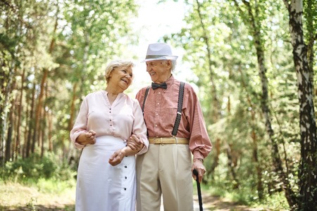 chilling out: Affectionate seniors in smart casual talking while chilling out in park