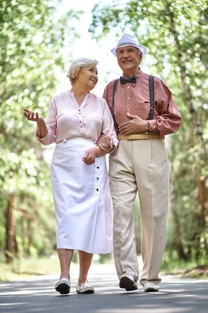 Affectionate seniors chilling out in park in summer
