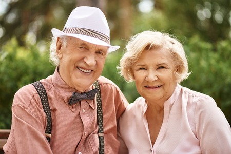 Cheerful seniors looking at camera with smiles outdoors