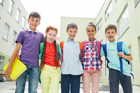 elementary schools: Row of successful learners looking at camera outside