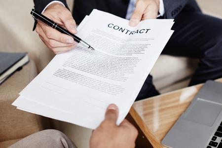 contrato de trabajo: empresario manos con la pluma y el contrato que le da al socio de la firma
