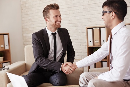 business partners: Business partners handshaking in office before meeting
