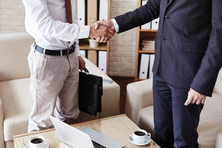 handshaking: Successful businessmen handshaking after signing contract in office
