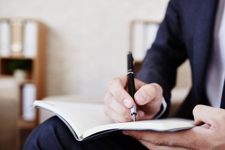 hombre escribiendo: Varón que hace notas en el bloc de notas de los empleados