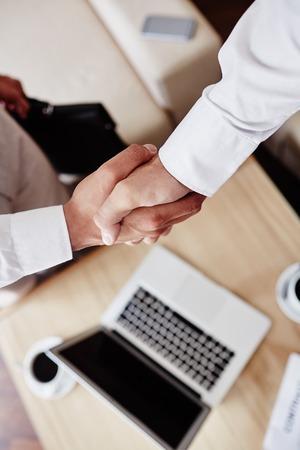 handshaking: Businessmen handshaking over laptop on workplace