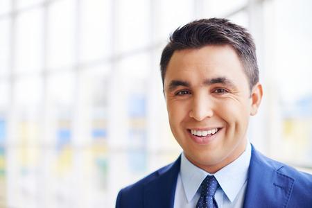 Gelukkig zakenman op zoek naar camera met een glimlach