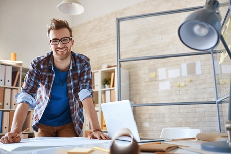 Contemporary engineer looking at camera during work in office Standard-Bild