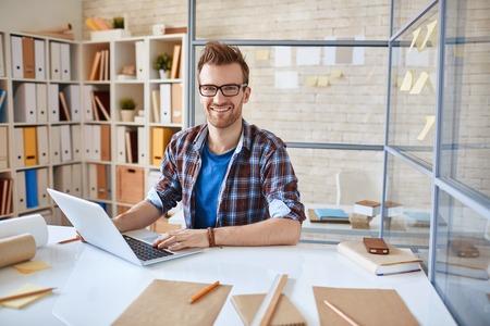 Happy zakenman zitten op de werkplek en kijken naar de camera