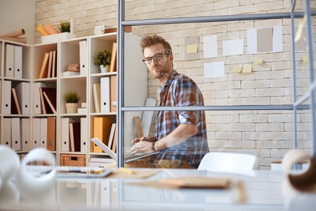 architect office: Serious architect working with laptop in office Stock Photo