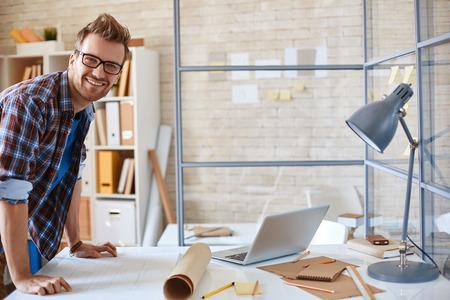 happy employee: Happy young employee looking at camera in office Stock Photo
