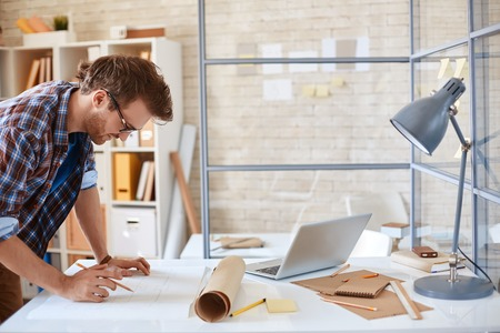 Modern architect looking at blueprint with sketch of construction in office