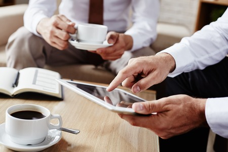 touchpad: Businessman pointing at screen of touchpad during explanation of data