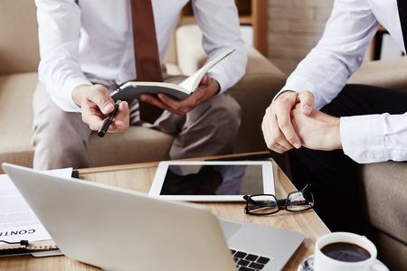 2 人の従業員のラップトップのデータを議論し、自分たちのノートをコンサルティング 写真素材