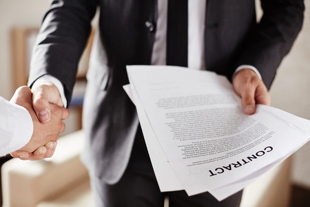 contrato de trabajo: El hombre de negocios con un contrato de apretón de manos con el socio Foto de archivo