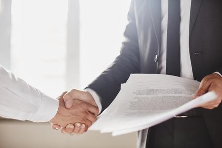 Zakenman met documenten feliciteren met zijn partner Stockfoto