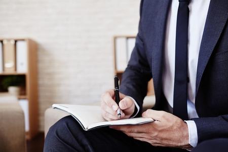 persona escribiendo: Empleado Hombre con la pluma y la escritura libreta plan de Foto de archivo