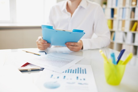 financial executive: Male employee with clipboard sitting at workplace