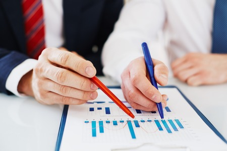 information point: Two colleagues with pens pointing at document
