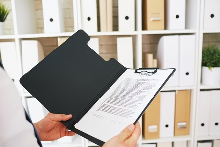 clipboard: Businessman holding open folder with text of contract