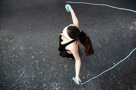 activewear: Girl in activewear exercising with skipping-rope