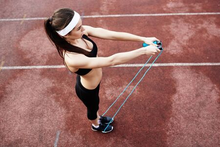 sports training: Girl with skipping-rope training at stadium