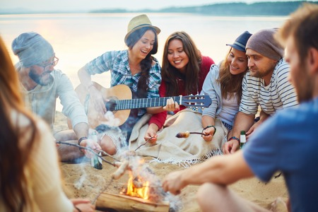 campfires: Friendly girls and guys having great time on sandy beach by campfire