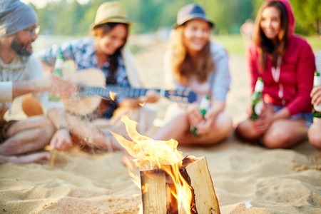 restful: Burning wood on background of restful friends Stock Photo