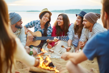 camp: Friendly girls and guys singing by guitar by campfire Stock Photo