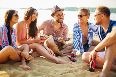 amigas: Amigos felices con las bebidas sentado en la arena por el agua