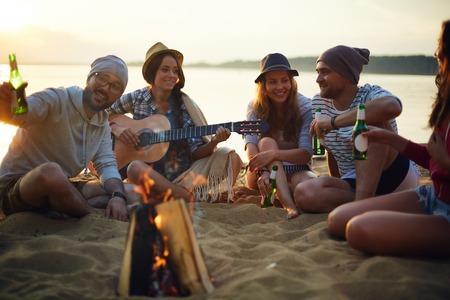 Amigos felices con bebidas y guitarra que se sienta por la hoguera