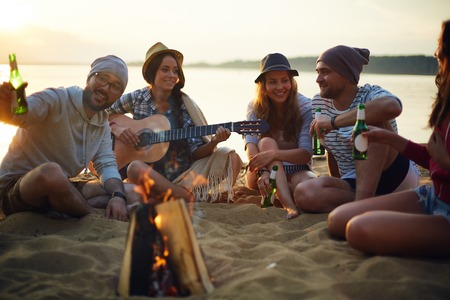 gitara: Szczęśliwi przyjaciele z napojami i gitara siedzi przy ognisku