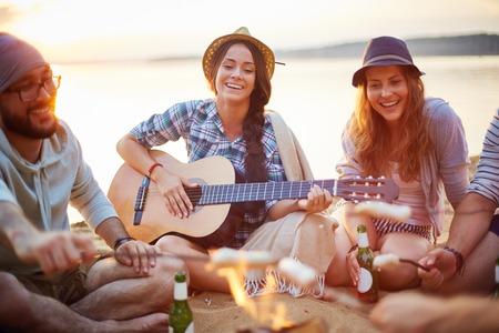 persona cantando: Niñas de amistad con la guitarra y la bebida cantando en la playa arenosa por fogata entre amigos Foto de archivo