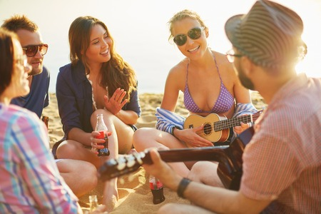 relaxing beach: Restful friends with drinks and guitar spending leisure on sandy beach