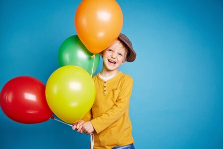 child smile: Little boy with balloons over blue background