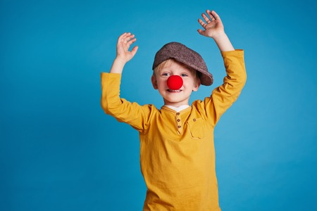 Portrait of cute boy with clown nose on blue background