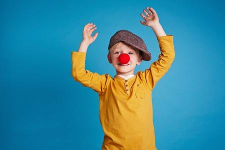 payaso: Retrato de niño lindo con nariz de payaso sobre fondo azul